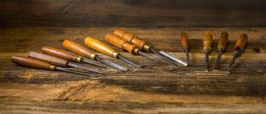 Grupo do formão de madeira para cinzelar a madeira, ferramentas da escultura no fundo de madeira fotografia de stock