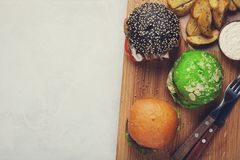 Grupo do mini hamburguer três caseiro com carne e os vegetais de mármore em uma placa de madeira o conceito da comida lixo e do f Imagem de Stock Royalty Free