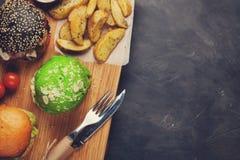 Grupo do mini hamburguer três caseiro com carne e os vegetais de mármore em uma placa de madeira o conceito da comida lixo e do f Fotografia de Stock