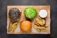 Grupo do mini hamburguer três caseiro com carne e os vegetais de mármore em uma placa de madeira o conceito da comida lixo e do f Imagens de Stock Royalty Free