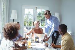 Grupo do portátil de utilização executivo ao comer o café da manhã Fotografia de Stock