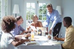Grupo do portátil de utilização executivo ao comer o café da manhã Foto de Stock Royalty Free