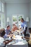 Grupo do portátil de utilização executivo ao comer o café da manhã Imagem de Stock Royalty Free
