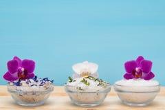 Grupo do sal branco com os aditivos para tratamentos dos termas, e orquídeas foto de stock