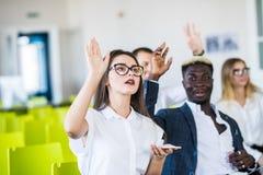 Grupo do seminário que levanta acima a mão para pedir o orador no tempo da pergunta e resposta na sala de reunião imagem de stock royalty free