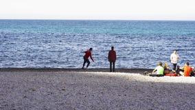 Grupo dos amigos que relaxam no litoral, stowns de jogo na água e tendo um piquenique, Oceano Pacífico, Califórnia filme