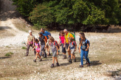 Grupo dos caminhantes, famílias com crianças, em uma caminhada da montanha imagem de stock