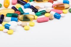 Grupo dos comprimidos e das cápsulas no branco Fotos de Stock