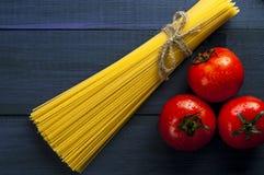 Grupo dos espaguetes e dos três tomates fotografia de stock