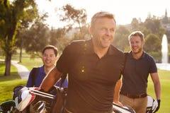Grupo dos jogadores de golfe masculinos que andam ao longo dos sacos levando do fairway fotografia de stock