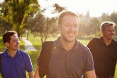 Grupo dos jogadores de golfe masculinos que andam ao longo dos sacos levando do fairway imagem de stock