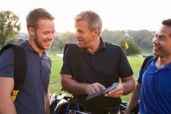 Grupo dos jogadores de golfe masculinos que marcam o marcador no fim de redondo foto de stock royalty free
