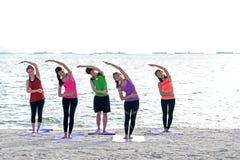 Grupo dos povos de Ásia que faz o guerreiro levantar na praia, na aptidão, no esporte, na ioga e no estilo de vida saudável imagem de stock royalty free
