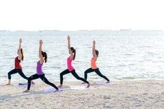 Grupo dos povos de Ásia que faz o guerreiro levantar na praia, na aptidão, no esporte, na ioga e no estilo de vida saudável imagens de stock