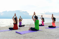 Grupo dos povos de Ásia que faz o guerreiro levantar na praia, na aptidão, no esporte, na ioga e no estilo de vida saudável fotografia de stock