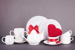 Grupo dos pratos brancos para o almoço e o chá com elementos da decoração dos corações vermelhos e das fitas do cetim em um fundo Fotografia de Stock Royalty Free