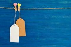 Grupo dos preços ou de etiquetas do papel vazio e pinos de madeira decorados nos corações que penduram em uma corda no fundo de m Imagens de Stock