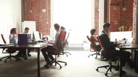Grupo dos trabalhadores de escritório que usa o funcionamento do PC que fala em coworking moderno vídeos de arquivo