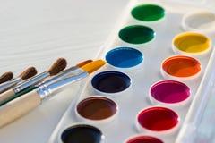 Grupo e escovas novos coloridos da bandeja da pintura da aquarela Fotografia de Stock Royalty Free