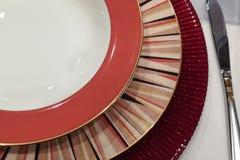 Grupo elegante vazio da tabela de uma textura diferente de três placas e cor nas sombras vermelhas que servem em uma tabela foto de stock