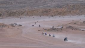 Grupo em passeios da bicicleta do quadril?tero atrav?s do deserto em Egito no contexto das montanhas Conduzindo ATVs video estoque