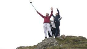 Grupo emocionado de turistas que se divierten que toma el selfie en amistad y la libertad de celebración superiores de la montaña metrajes