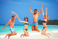 Grupo emocionado feliz de amigos jovenes que saltan en la playa del verano Foto de archivo