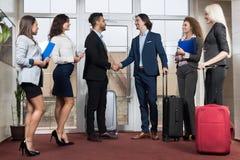 Grupo en pasillo, dos hombre de negocios Meeting Handshake de Meeting Business People del recepcionista del hotel Imágenes de archivo libres de regalías