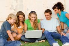 Grupo feliz con la computadora portátil Foto de archivo