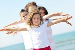 Grupo feliz da criança que joga na praia Imagens de Stock Royalty Free