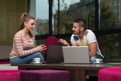 Grupo feliz de adolescentes en el café usando el ordenador portátil Imagen de archivo libre de regalías