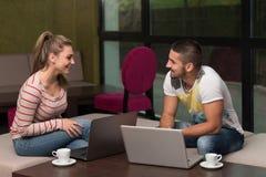 Grupo feliz de adolescentes en el café usando el ordenador portátil Fotografía de archivo libre de regalías