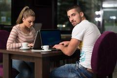 Grupo feliz de adolescentes en el café usando el ordenador portátil Imagen de archivo
