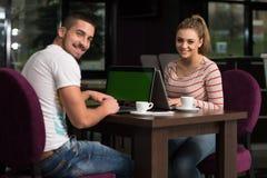 Grupo feliz de adolescentes en el café usando el ordenador portátil Fotos de archivo