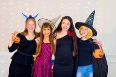 Grupo feliz de adolescentes en los disfraces de Halloween que presentan en cámara Imagenes de archivo