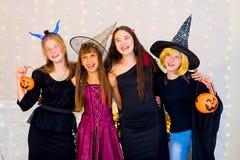 Grupo feliz de adolescentes en los disfraces de Halloween que presentan en cámara Fotografía de archivo