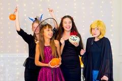 Grupo feliz de adolescentes en los disfraces de Halloween que presentan en cámara Fotos de archivo libres de regalías