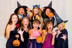 Grupo feliz de adolescentes en los disfraces de Halloween que presentan en cámara Fotos de archivo