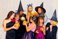 Grupo feliz de adolescentes en los disfraces de Halloween que presentan en cámara Foto de archivo