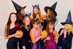 Grupo feliz de adolescentes en los disfraces de Halloween que presentan en cámara Imagen de archivo libre de regalías