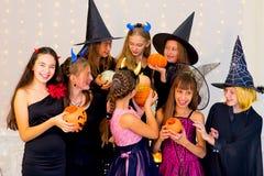 Grupo feliz de adolescentes en los disfraces de Halloween que presentan en cámara Imagen de archivo