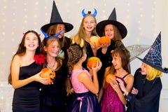 Grupo feliz de adolescentes en los disfraces de Halloween que presentan en cámara Foto de archivo libre de regalías