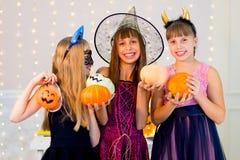 Grupo feliz de adolescentes en los disfraces de Halloween que presentan en cámara Imágenes de archivo libres de regalías