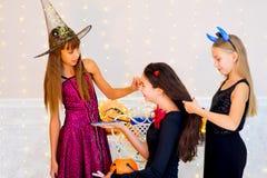 Grupo feliz de adolescentes en los trajes que se preparan para Halloween Fotos de archivo