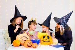 Grupo feliz de adolescentes en los trajes que se preparan para Halloween Foto de archivo libre de regalías