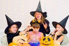Grupo feliz de adolescentes en trajes durante el partido de Halloween Imagenes de archivo