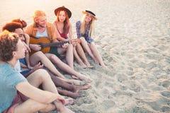 Grupo feliz de amigo que tiene partido en la playa Imagen de archivo