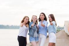 Grupo feliz de amigos fêmeas com os polegares acima da câmera de vista exterior e do sorriso imagens de stock
