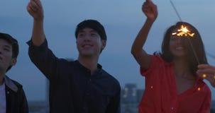 Grupo feliz de amigos jovenes gozar y jugar de la bengala en el partido del top del tejado en la igualación de puesta del sol Cel almacen de metraje de vídeo
