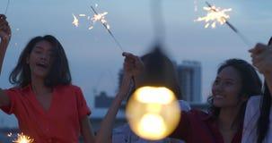 Grupo feliz de amigos jovenes gozar y jugar de la bengala en el partido del top del tejado en la igualación de puesta del sol Cel metrajes